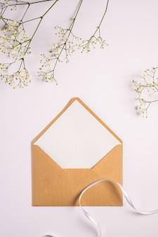 Kraft bruine papieren envelop met witte lege kaart, gypsophila bloemen en stoffen lint, witte achtergrond, mockup lege brief