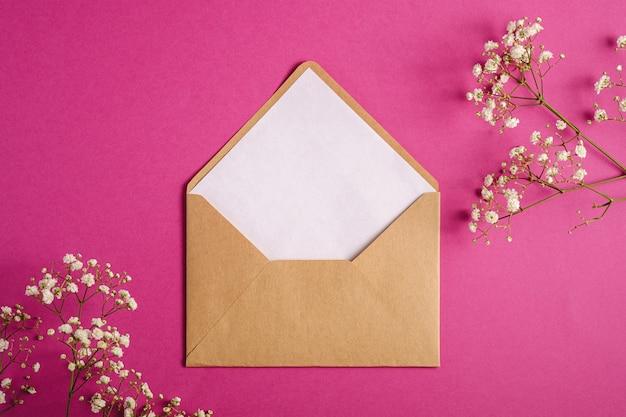 Kraft bruine papieren envelop met witte lege kaart, gypsophila bloemen, paars roze achtergrond, mockup lege brief