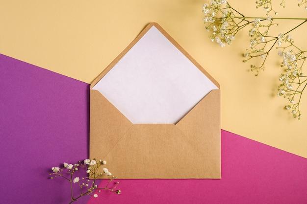 Kraft bruine papieren envelop met witte lege kaart, gypsophila bloemen, paarse en crème gele achtergrond, mockup sjabloon