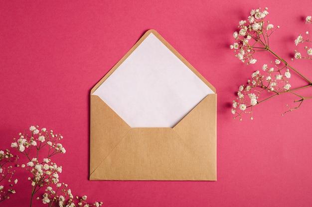 Kraft bruine papieren envelop met witte lege kaart, gypsophila bloemen, rood roze achtergrond, mockup sjabloon