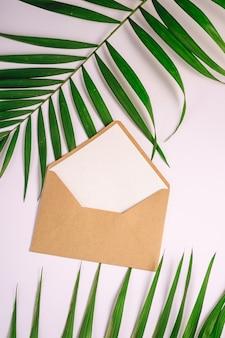 Kraft bruine papieren envelop met witte lege kaart op palmbladeren, witte achtergrond, mockup lege brief
