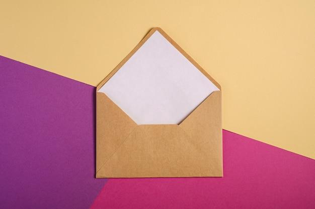 Kraft bruine papieren envelop met witte lege kaart, roze, paars en crème gele achtergrond, mockup lege brief