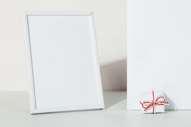 Kraft cadeau met een rood lint en fotolijst op een wit