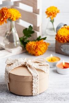 Kraft geschenkdoos en oranje bloemen in glazen pot