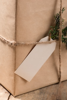 Kraftpapier doos en groene bladeren op woodean achtergrond.