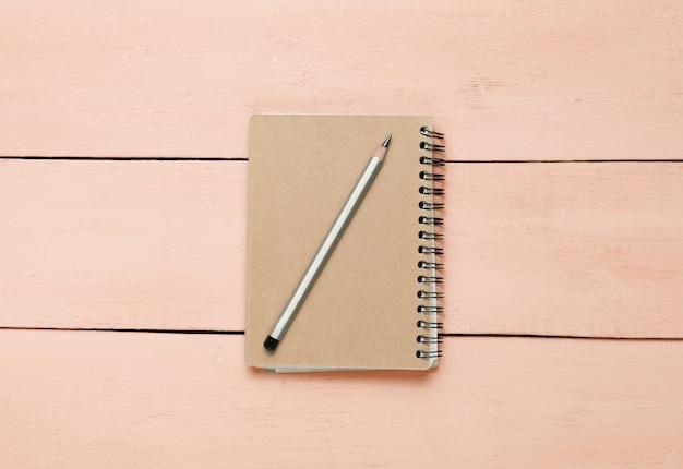 Kraftpapier-notitieblok met potlood op roze houten tafel