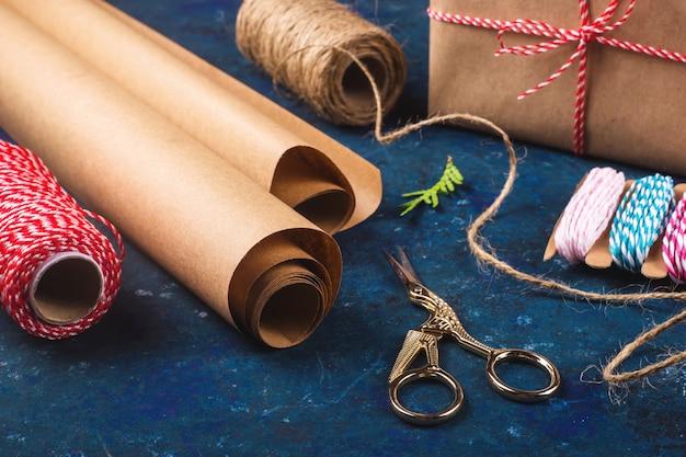 Kraftpapier voor het inpakken van geschenken naast een schaar en verschillende touwen. bereid je voor op kerst concept.