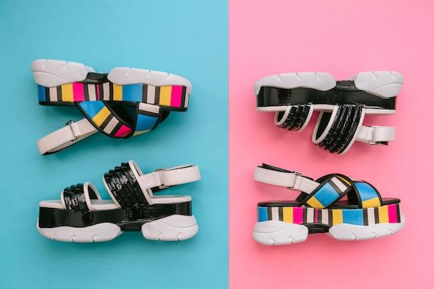 Krakau, polen - 25 april 2019: set modieuze vrouwelijke schoenen. sandalen van de zomer trendy veelkleurige vrouwen op hoge wig op blauwe en roze achtergrond. stoer en stijlvol schoeisel voor moderne meisjes.