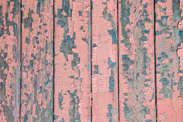 Krakende en afbladderende roze verf op een muur