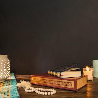 Kralen en boeken in de buurt van lantaarn en kaars