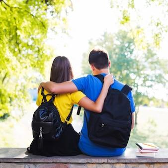 Kramende tieners zitten op hek