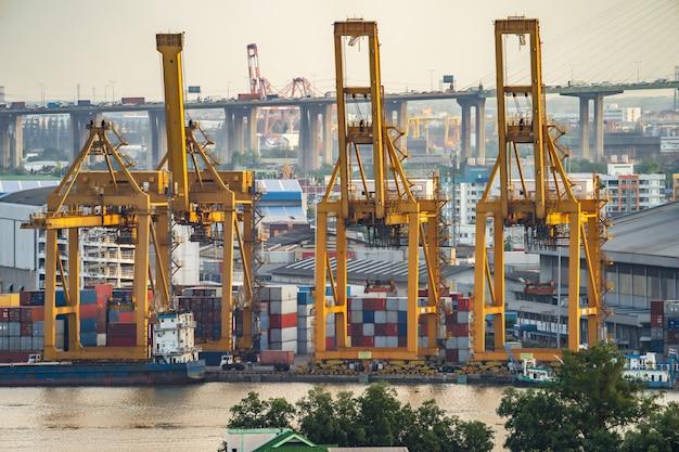 Kranen en industriële vrachtschepen in de haven bij schemering.