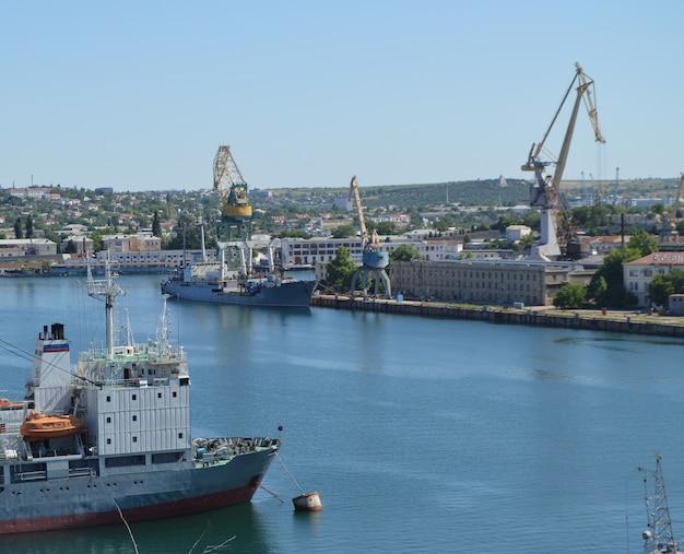 Kranen en schepen in vrachthaven, havenwatergebied, logistiekconcept