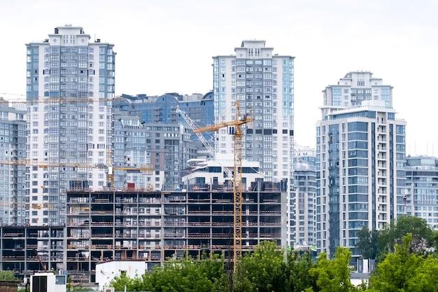 Kranen op een bouwplaats van de bouw van een moderne woonwijk hoge flatgebouwen of wolkenkrabbers in een nieuw elite-complex.