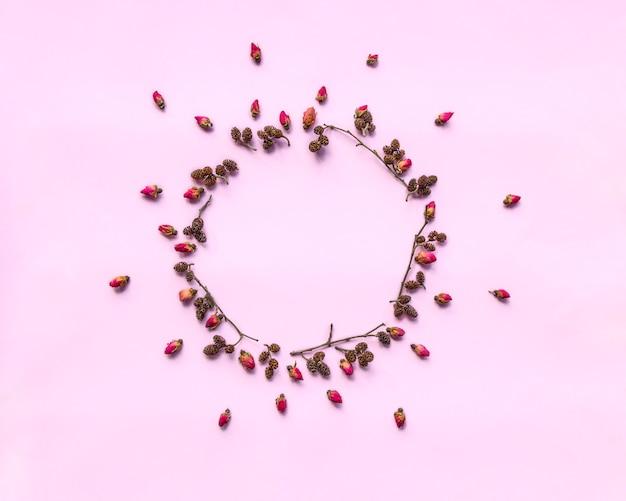 Krans gemaakt van verse rode rozen en twijgen met elzen kegels op roze achtergrond.