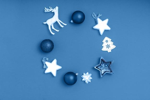 Krans van blauwe ballen, witte sterren, chrismas-boom, herten op blauwe ondergrond