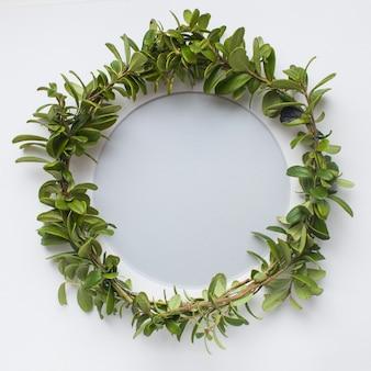 Krans van bosbessen bladeren en een ronde frame op witte achtergrond