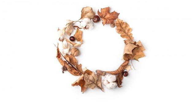 Krans van herfstbloemen, katoen en eikenbladeren, kastanje op wit