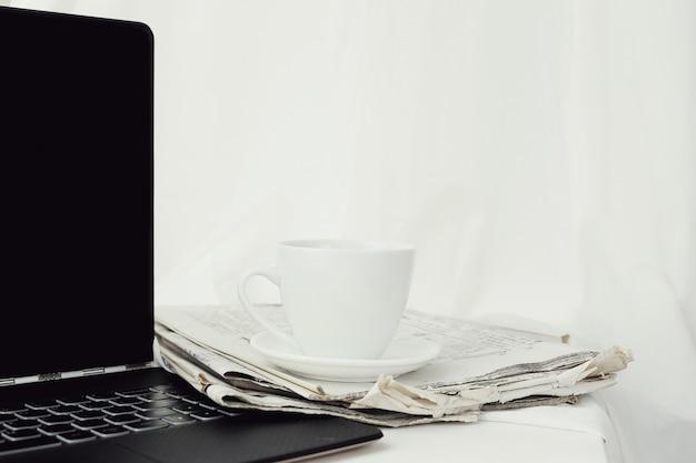 Krant met koffiekopje en laptop