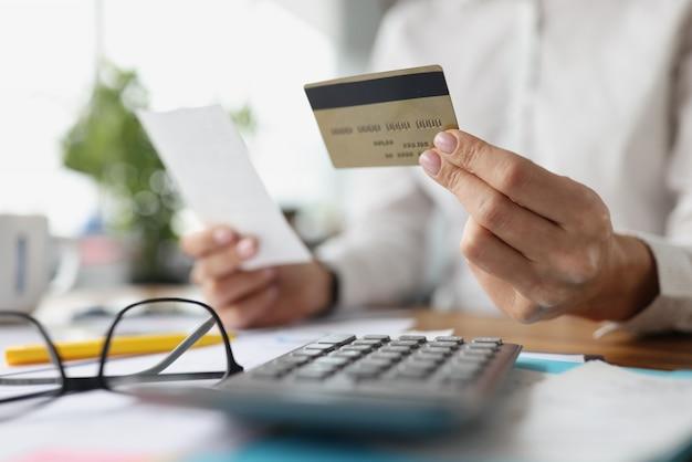 Krediet plastic bankkaart en check in vrouwelijke handen bankdiensten en geldoverdrachten concept