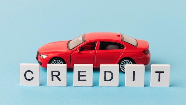 Kredietwoord naast een rode auto