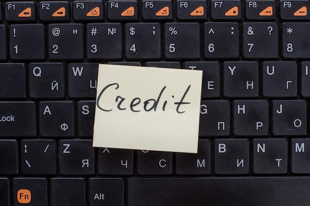 Kredietwoorden geschreven op notitiepapier. opmerking over het zwarte toetsenbord.