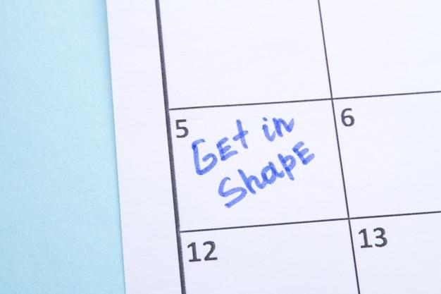 Krijg in vormherinnering geschreven door blauwe markering in een kalenderplanning om sportoefeningen te gaan doen om ...
