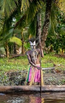 Krijger van de asmat-stam in een traditioneel masker op een kano.