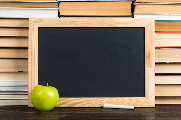 Krijtbord, appel en krijt, tegen boeken, exemplaarruimte.