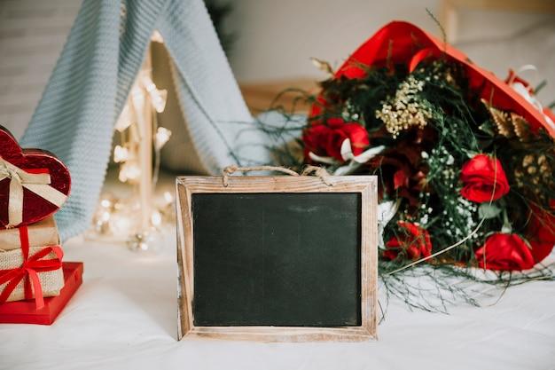 Krijtbord dichtbij boeket en stapel van cadeaus