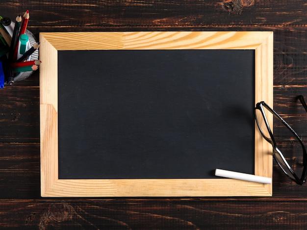 Krijtbord, glazen en krijt op een houten lijst, exemplaarruimte.