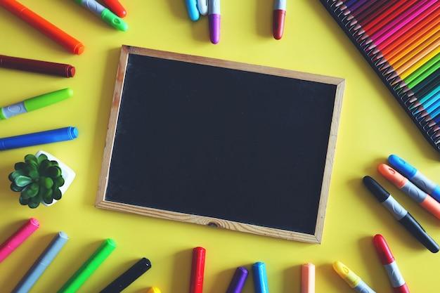 Krijtbord met gekleurde markeringen en potloden op gele achtergrond. schoolbenodigdheden voor kinderen. bovenaanzicht.