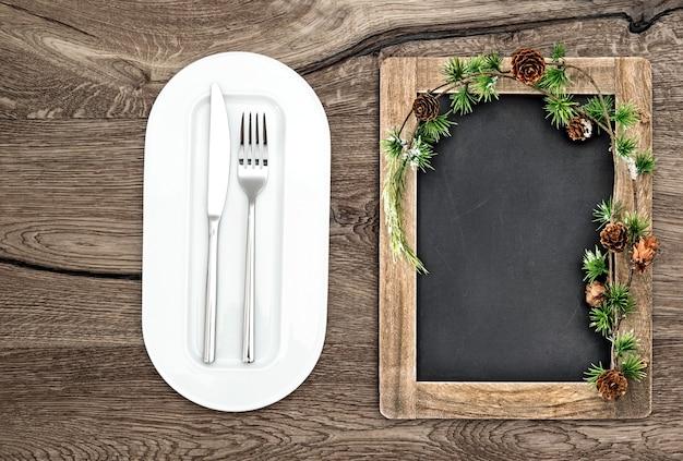 Krijtbord met kerstboomtakken op houten tafel. kerst, nieuwjaar, wintermenuconcept