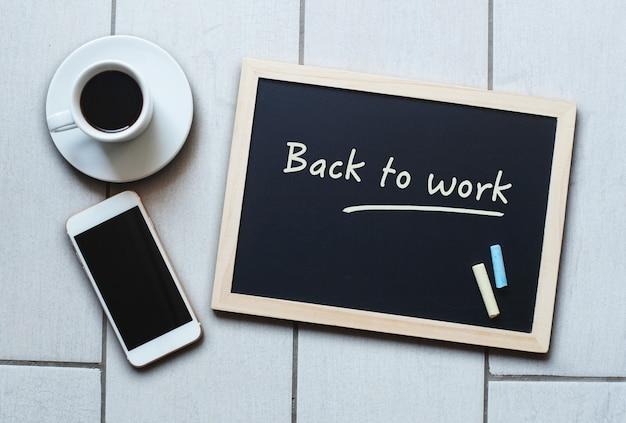 Krijtbord of blackboard-concept dat 'back to work' zegt met koffie en mobiele telefoon