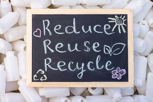 Krijtbord reduse hergebruik recycle teken op de achtergrond van lege plastic verpakkingen. bovenaanzicht.