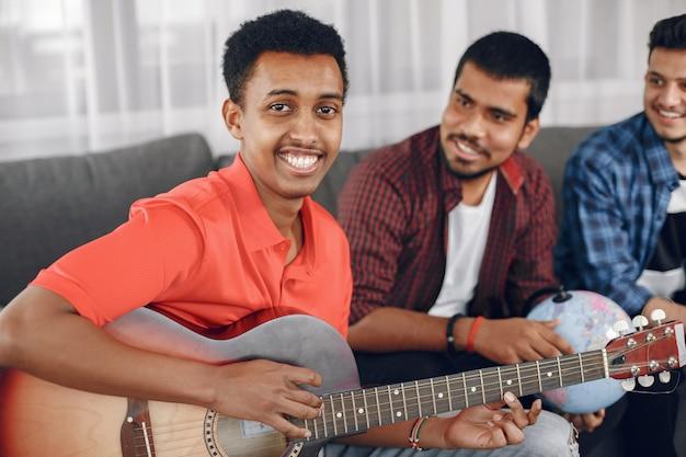 Kring van diverse frineds verzamelden zich thuis. een man zingt terwijl hij gitaar speelt.