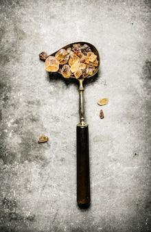 Kristalbruine suiker in een oude lepel. op een stenen tafel.