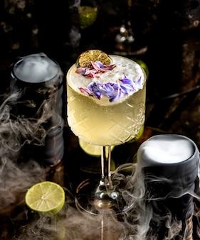 Kristalglas limoen cocktail gegarneerd met bloemblaadjes
