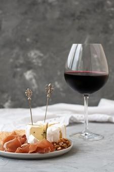 Kristalglas met rode wijn, op de voorgrond een bord met ham, noten, crackers en camembert kaas