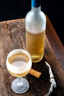 Kristalglas met witte wijn en een fles wijn die erg koud werd geserveerd op een rustieke houten tafel