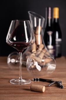 Kristalglas rode wijn, flessen, kurkentrekker, karaf, kurken op houten tafel