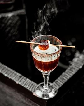 Kristalglas van hete cocktail gegarneerd met geroosterde marshmallow op spiesjes