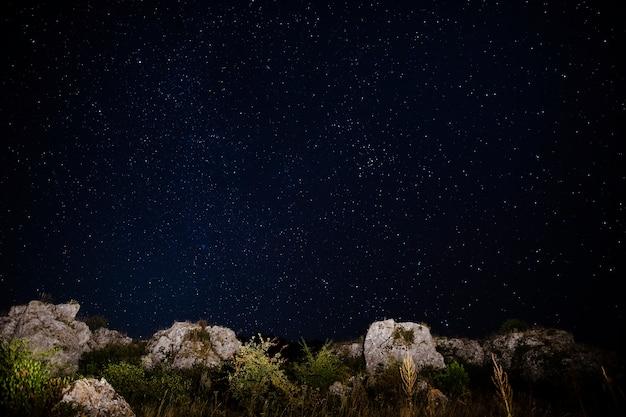 Kristalheldere hemel met sterren en rotsen op de grond