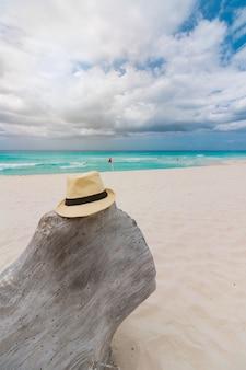 Kristalheldere zee met wit zand en wolkenlucht.