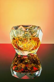 Kristallen beker met elite whisky en ijsblokjes op een verloop met reflectie
