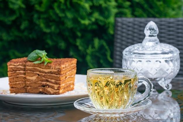 Kristallen beker met muntthee, suikerpot en medovik cake op tafel in het zomercafé