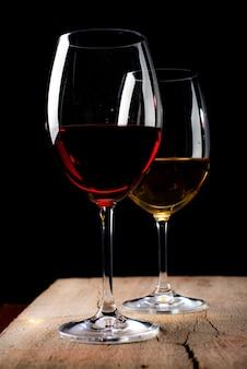Kristallen glazen met rode en witte wijn over rustieke houten tafel