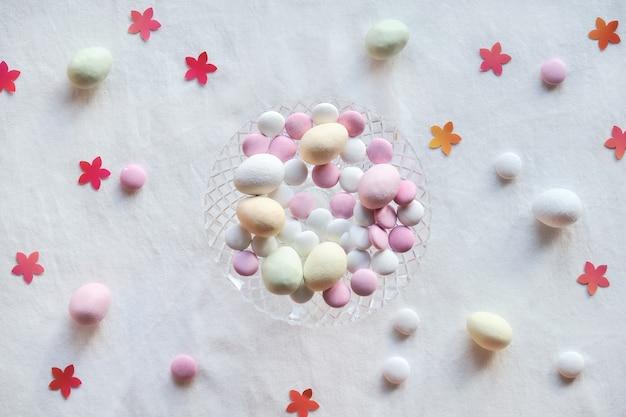 Kristallen glazen vaas met marsepein paaseieren en chocoladesuikergoed op wit textiel