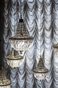 Kristallen kroonluchters op de achtergrond van gordijnen