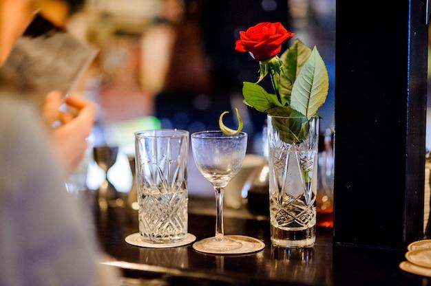Kristallen vaas met rode roos, een leeg glas en een half gevuld glas met water staan op een toog